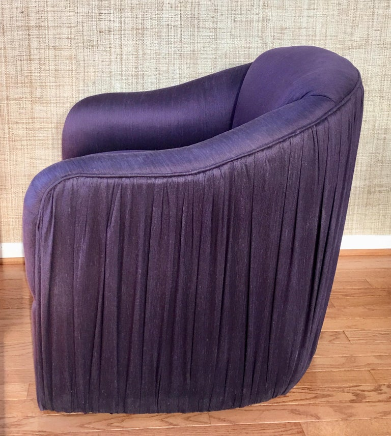 Unique and sculptural lounge chair with matching round soufflé pouf ottoman featuring original aubergine or purple toned fabric. Design details of this custom seating set includes ruched or pleated fabric on outside back/sides of chair and on the