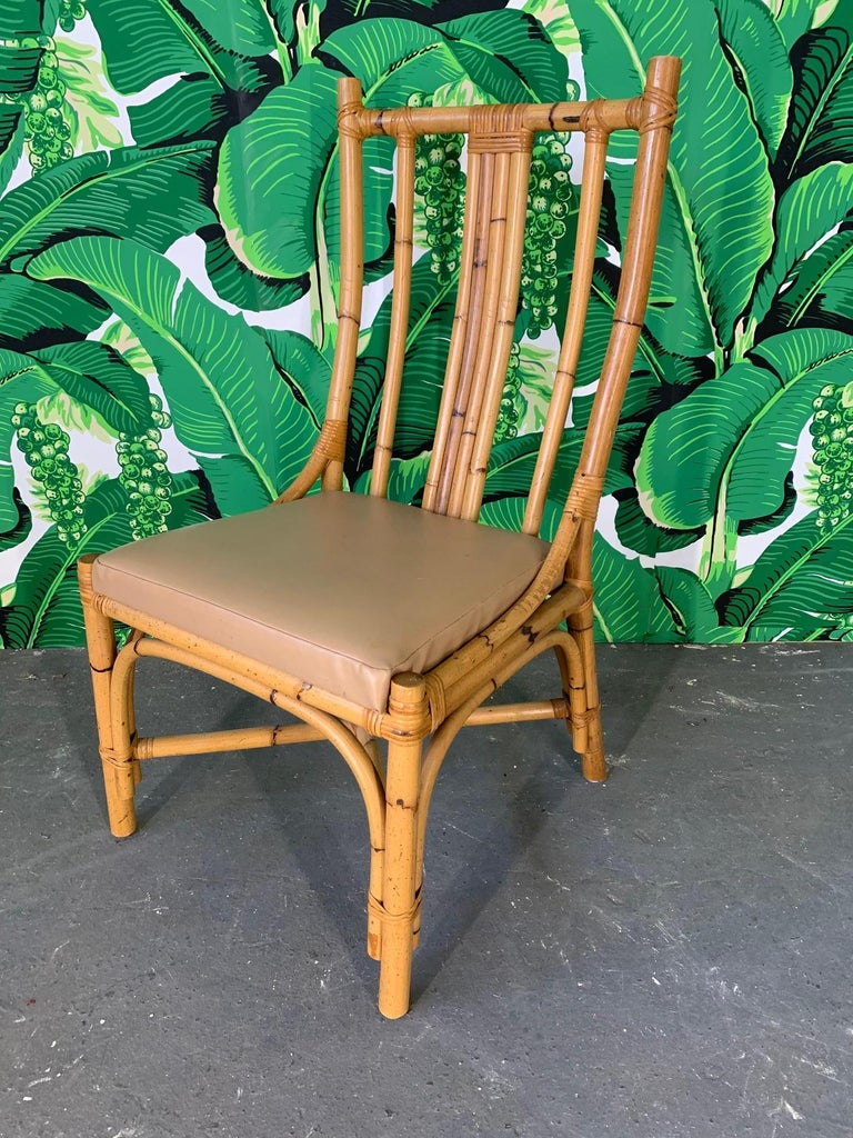 Set of 6 rattan dining chairs with sculptural form. Vinyl seat cushions that could easily be recovered. Very good vintage condition with minor imperfections consistent with age.