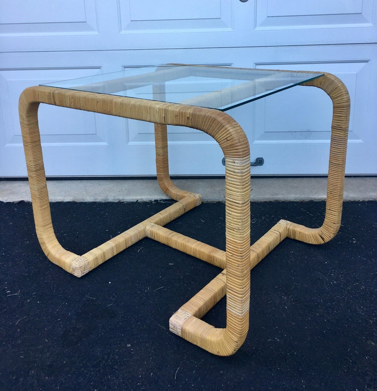 Vintage Mid-Century Modern rattan wrapped side or end table with clear glass top. Sculptural wood frame features an H-shaped base wrapped in natural toned rattan. Can be used as a bedside table or as a unique hall occasion center or cocktail table.