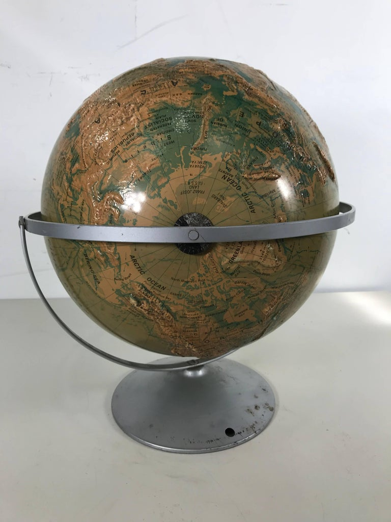 Sculptural relief world globe by Nystrom, wonderful design, aluminum stand, raised graphics, nice color and patina. Measures:16