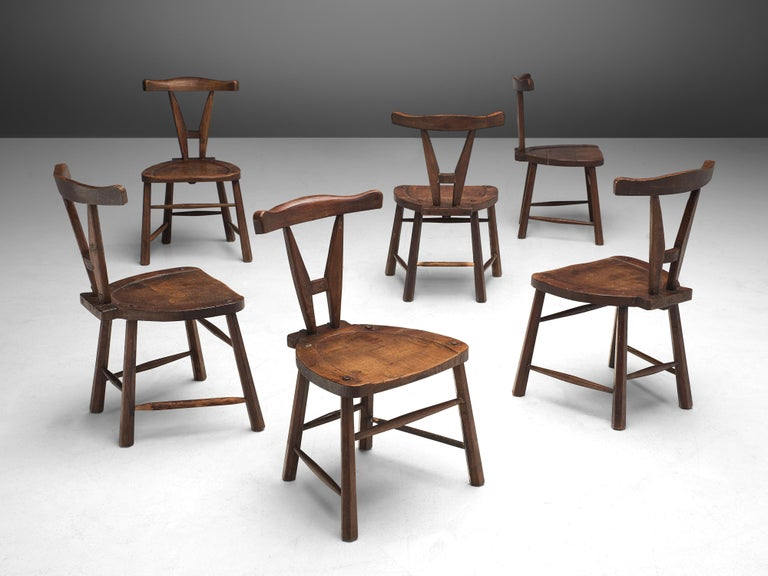 Set of 6 dining chairs, oak, France, 1940s  A robust set of carved wooden dining chairs. These chairs are made of stained oak and sculpturally crafted by hand. The craftsmanship is still visible, for instance, traces ofgouge cut are visible in the