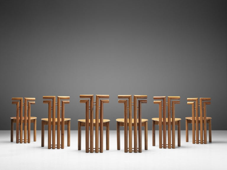 Set of six dining chairs, Italian walnut and cognac leather, Italy, 1970s.  Set of sculptural chairs that feature wonderful backrests, consisting of four legs that form out to the side, which creates a sculptural appearance. The front legs are