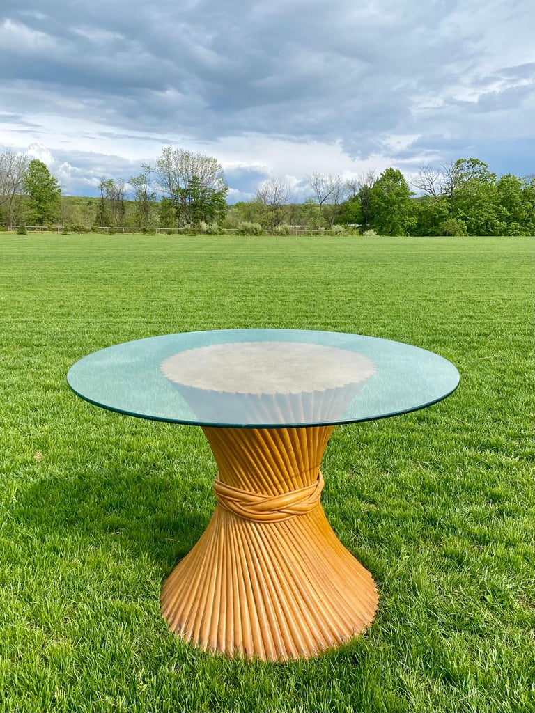 Sculptural Mid-Century Modern sheaf of wheat dining pedestal table, in the style of McGuire. This circular palm regency style table features bent and twisted rattan bamboo wood rods and round glass top. Original finish in natural tone wood with