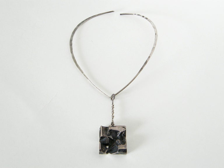 This deeply three-dimensional, abstract pendant was designed by Jorma Laine and made at the Finnish silver company Kultateollisuss Ky, in Turku and bears their hallmark. It comes together with a hammered sterling neck ring made by the Norwegian