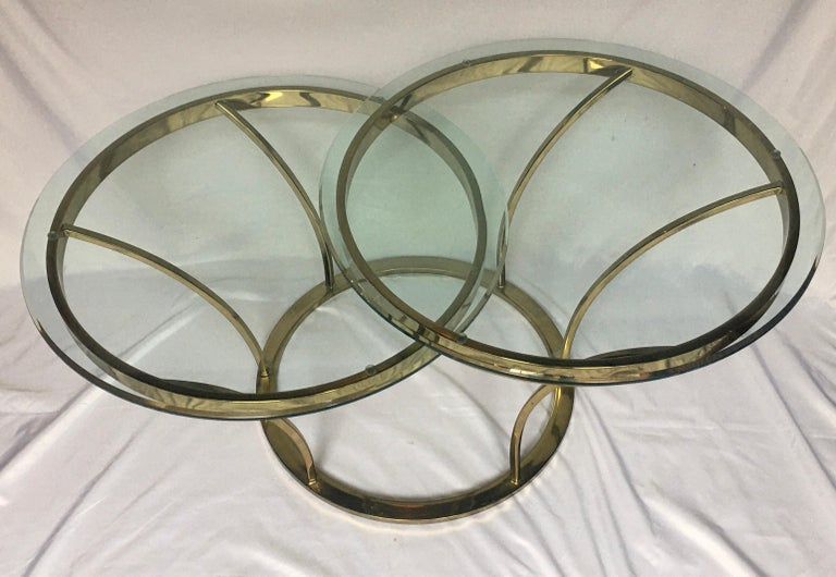 Sculptural 1970s brass-plated metal and glass center coffee or cocktail table. Sculptural curved design features two beveled round glass tops, tiered at different heights for a unique asymmetrical look. Style of Milo Baughman.  Top tier one: 25 W,