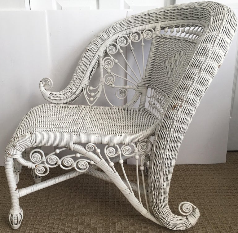 Victorian style white one-arm wicker portrait chair. This unique and sculptural lounging chair is the perfect accent piece for any space including a bedroom, living room or even in a large bathroom or walk-in closet. This chaise lounge style chair