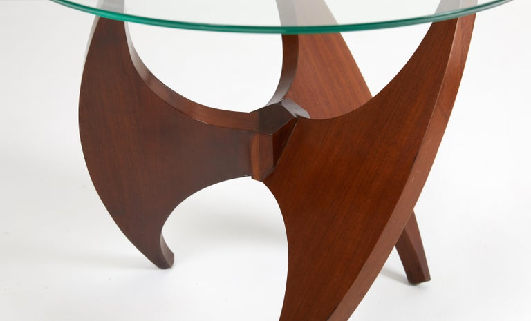 Beautiful solid walnut side table, circa 1950s. Sculptural propeller form base with glass top.