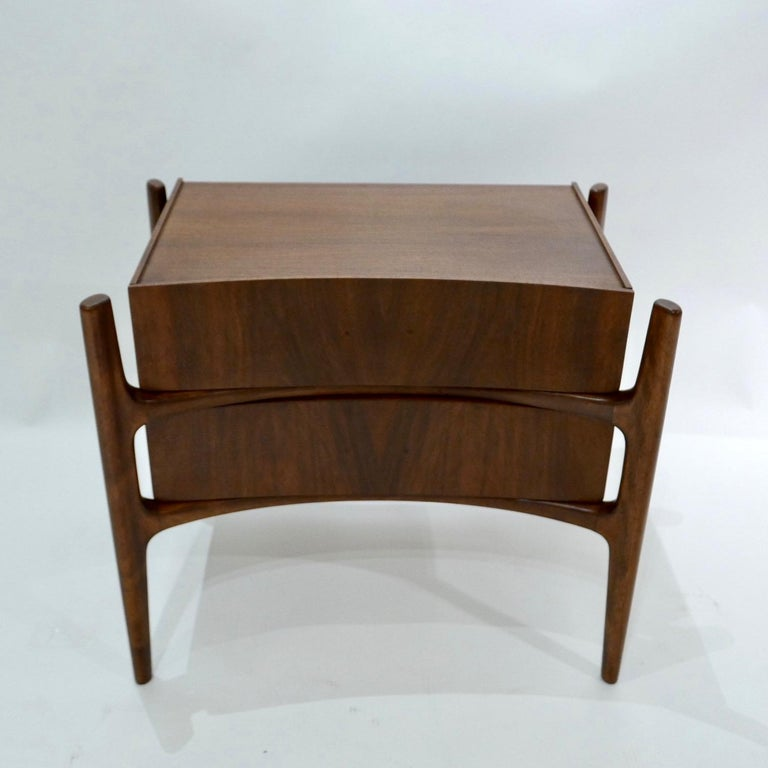 Exposed carved walnut legs with a curved bookmatched walnut front. Beautiful and Sculptural nightside table or nightstand designed by William Hinn for Urban Furniture's