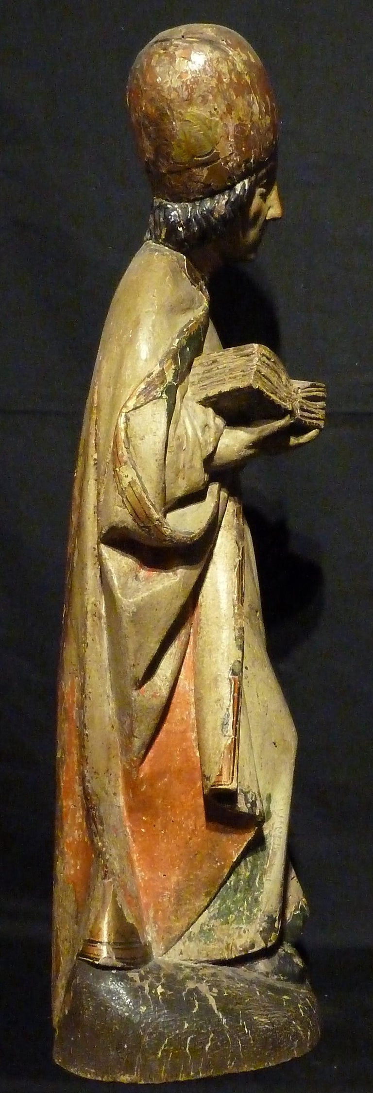Polychrome-decorated carved wood sculpture, wearing the vestments of a bishop, with book in his left hand. South Tyrol 15th century, measures: 57 cm H.