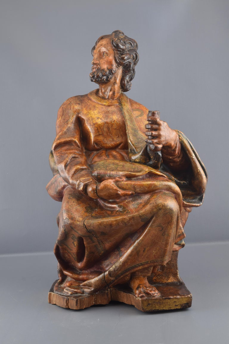 Male figure with dark hair and beard, dressed in tunic and mantle, sitting and with an object in his right hand. The iconographic attributes are not sufficient to identify it, being able to be an Evangelist or another of the Apostles. The anatomy,