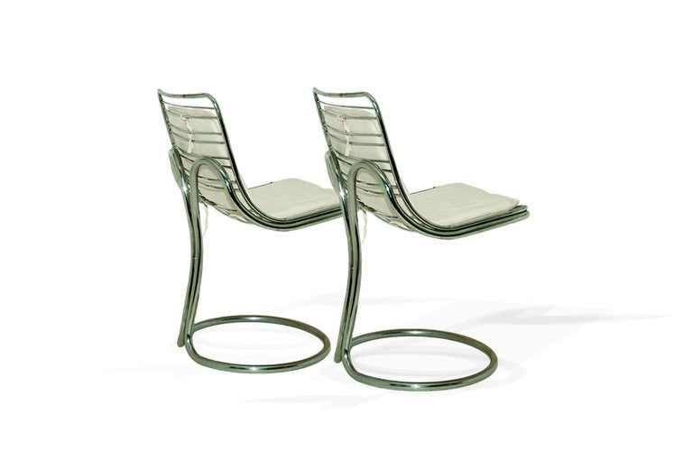 These chairs has, an extraordinary sculptural shape, made by the twist of the chromed metal tubes, in the back. The seats are covered with an amovible white Alcantara cover. The feet are in circle, a round shape, with the tubes forming a circle.