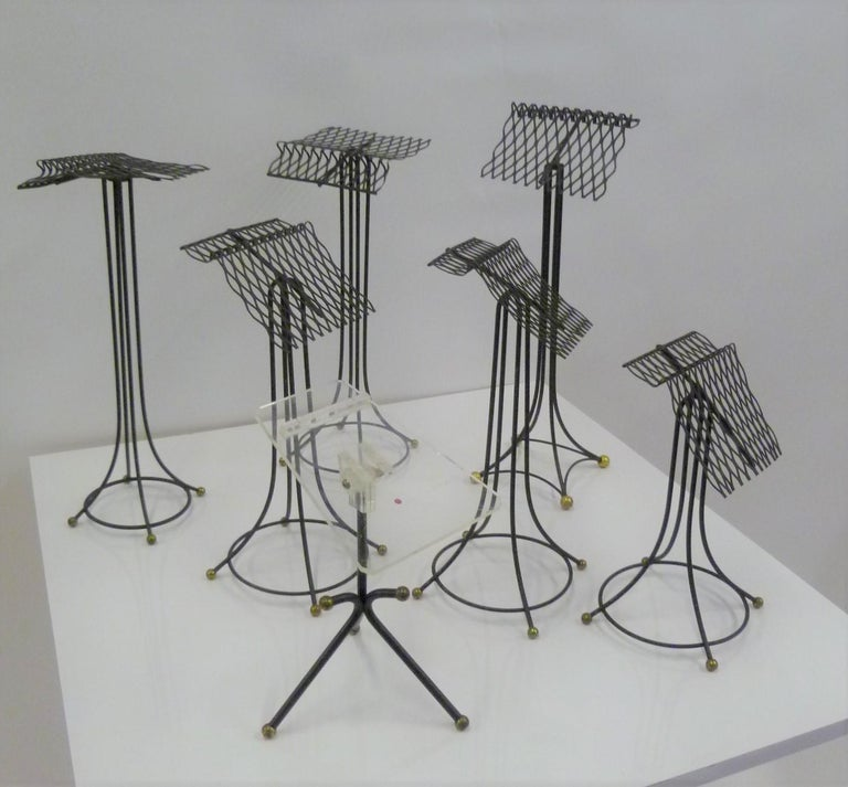 From the 1930s-40s sculptural group of 7 black metal store display stands, most likely for ladies shoes. Three different styles: one with a Lucite top, one with Eiffel tower base and 5 different heights with rounded base. In very good original