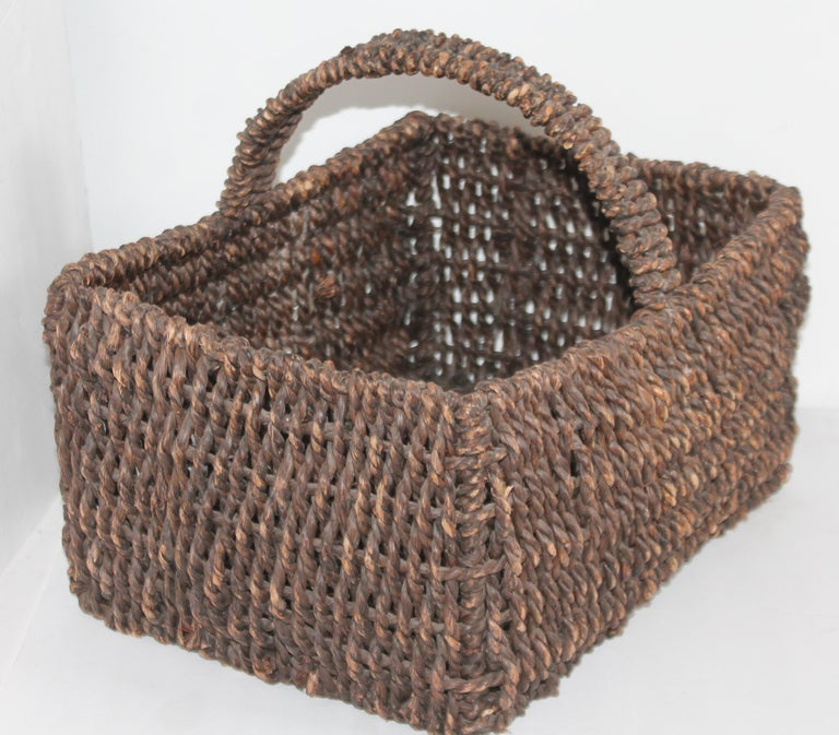 This funky sea grass basket is handwoven and in good condition. It retains its old surface.