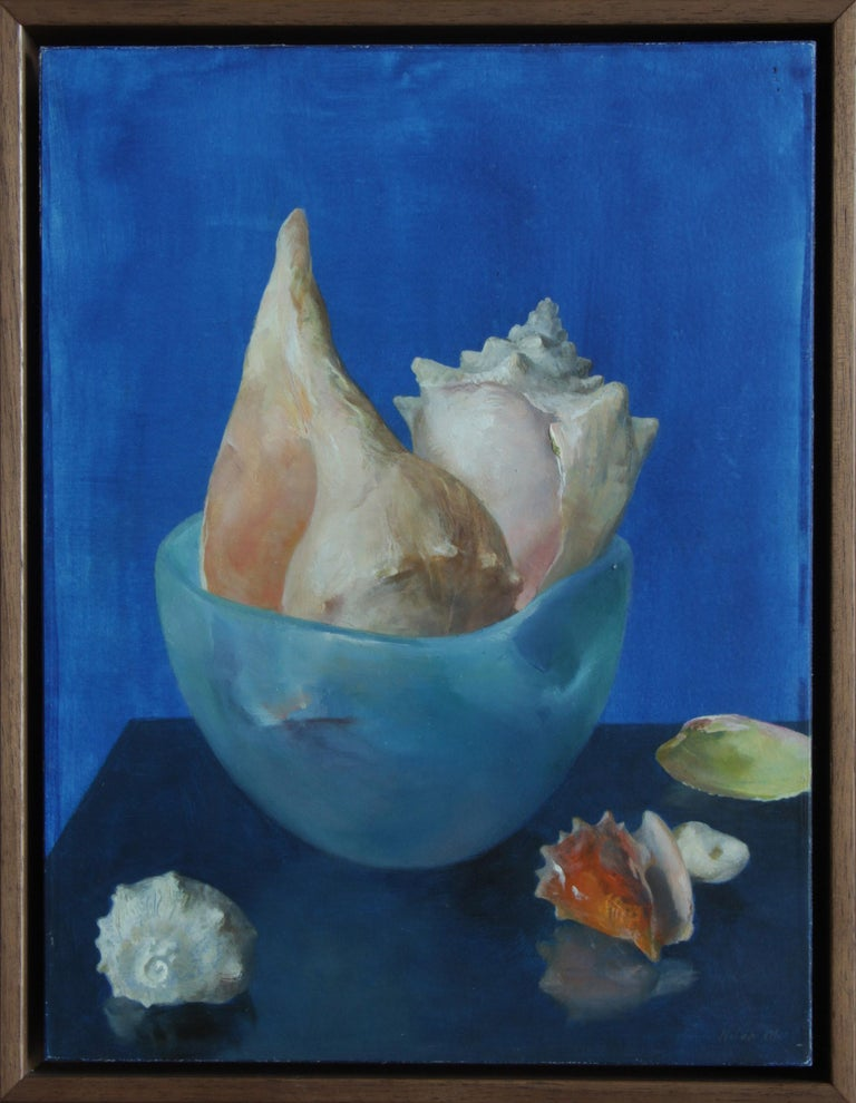 This delicately rendered painting presents the viewer with a study in contrasts. A collection of 6 seashells are arranged in a setting with three differing shades of blue. The shells are arranged, some in the ceramic glazed bowl and some sitting