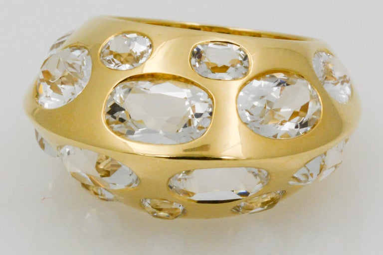 This Seaman Schepps Antibes ring is adorned in 18k yellow gold and features 14 oval white topaz. The ring has a domed peak design and is signed Seaman Schepps. The ring is currently a size six, and can be sized one (1) size up or down.