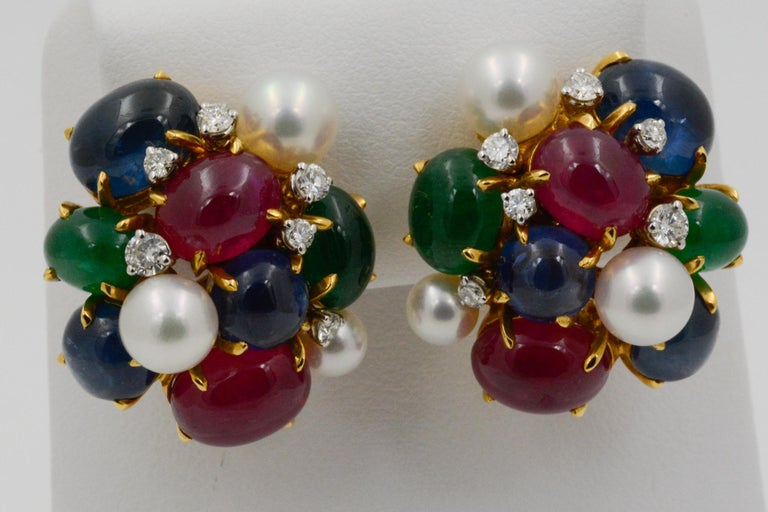 From Seaman Schepps, these 18k yellow gold Bubble clip earrings feature four oval cabochon rubies, four oval cabochon emeralds, four round cabochon blue sapphires, two oval cabochon blue sapphires, six white pearls, and 12 round brilliant cut