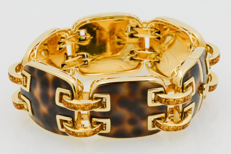 From Seaman Schepps, this 18k yellow gold Cowrie Ponte bracelet features five full square cushion shape cowrie links and two halves forming the clasp. The bracelet features 12 double connector bars, each channel is set with square faceted baguette