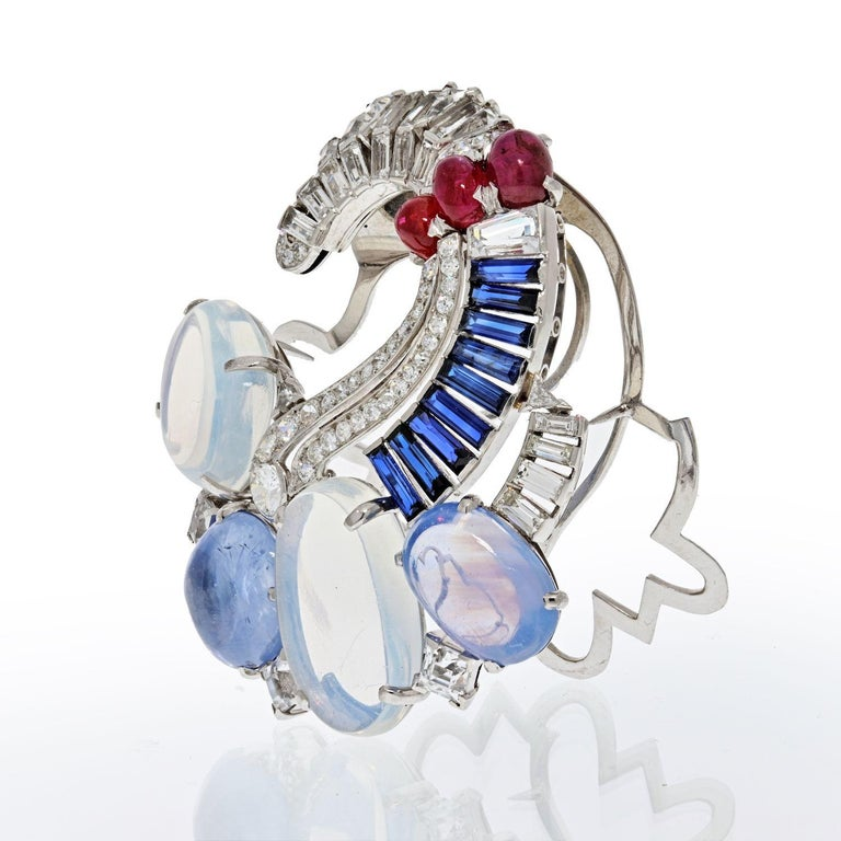 Absolutely stunning and one of a kind Seaman Schepps brooch with moonstone, diamonds, sapphires and rubies. Crafted from 18K white gold with 14K white gold clip. Lively color gemstones such as two large cabochon moonstones approx. 26.00 carats