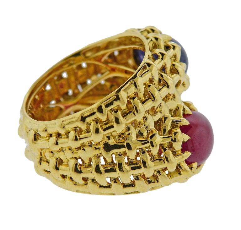 18k yellow god bypass ring by Seaman Schepps, featuring 10.5mm x 7.2mm sapphire and 10.7mm x 7.3mm ruby cabochons. Ring size - 7.5, ring top is 20mm wide, weighs 15.1 grams. Marked: 750, Shell hallmark.