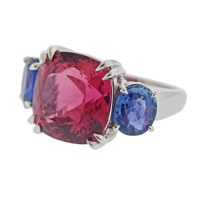 18k white gold ring by Seaman Schepps, set with approx. 15ct pink tourmaline, measuring 14.5mm x 14.6mm, and two oval sapphires on sides - approx. 8.3mm x 7.2mm and 8.5mm x 7mm. Ring size - 6.5, ring top - 14.5mm x 25mm. Weight is 13.6 grams. Marked