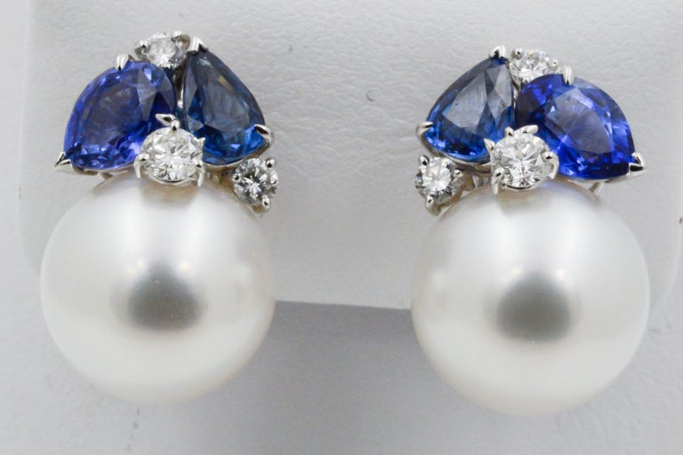 From Seaman Schepps, these 18k white gold feature 14mm white south sea pearl and four pear shaped blue sapphires (4.07ctw) and six round brilliant cut diamonds (.58ctw). Signed Seaman Schepps.