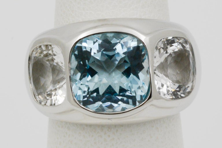 From Seaman Schepps, this 18k white gold three stone Mogul ring features one blue topaz, weighing a total of 5.62 carats and two white topaz sides weighing a total of 2.45 carats. The ring is a size 6.5.