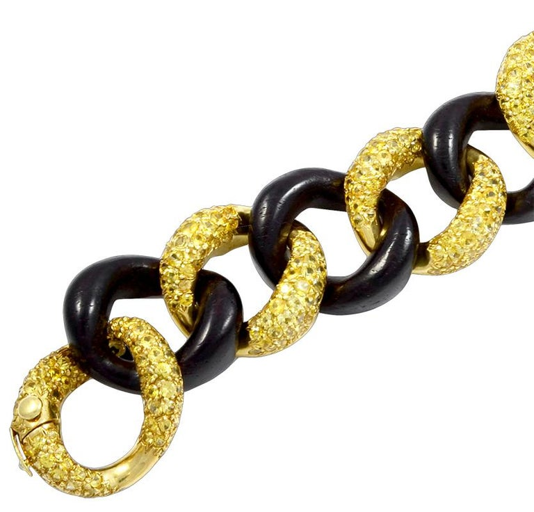 Exceptionally crafted by Seaman Schepps, comprising a vintage link bracelet crafted with interlocking links made of 18k yellow gold embellished with yellow sapphires and black wood, signed Seaman Schepps.