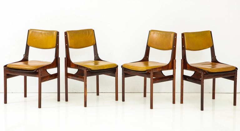 Set of four dining chairs in Jacaranda and Jacaranda plywood with original yellow ochre leather back cushions and loose seat cushions. Made in Sao Paulo, Brazil, circa 1965 by J.D. Movies e Decoracoes in a style inspired by Jorge Zalszupin. With one