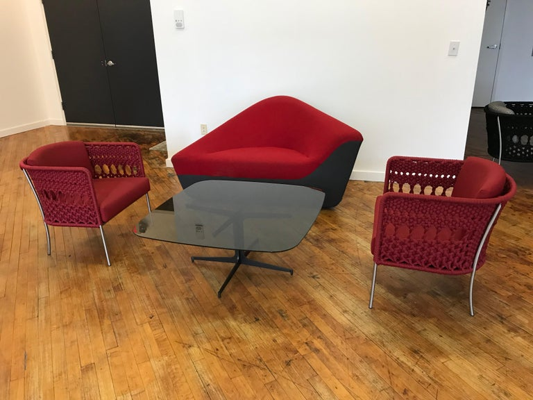 Seating stone lounge in tomato red fabric with steel and foam construction. Modern and contemporary in design and form, and functional as a chaise, small sofa or lounge for any living room space.   Details: 8055 tomato / 8202 slate steel