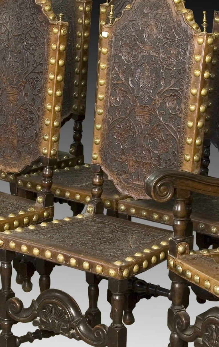 Seats in walnut and embossed leather, 19th century. Set of six chairs and two matching armchairs, made of walnut and with seat and back in embossed leather (some leathers require restoration). The structure is based on the traditional models of the