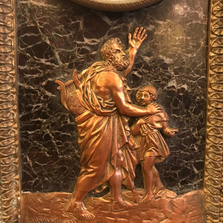 This fine French clock, in an arched verde antico marble case, is set with a bas relief panel depicting Homer. The declaiming blind poet carries his lyre, a young boy leading him. It is boldly framed in bronze and with a crisp broad acanthus band at