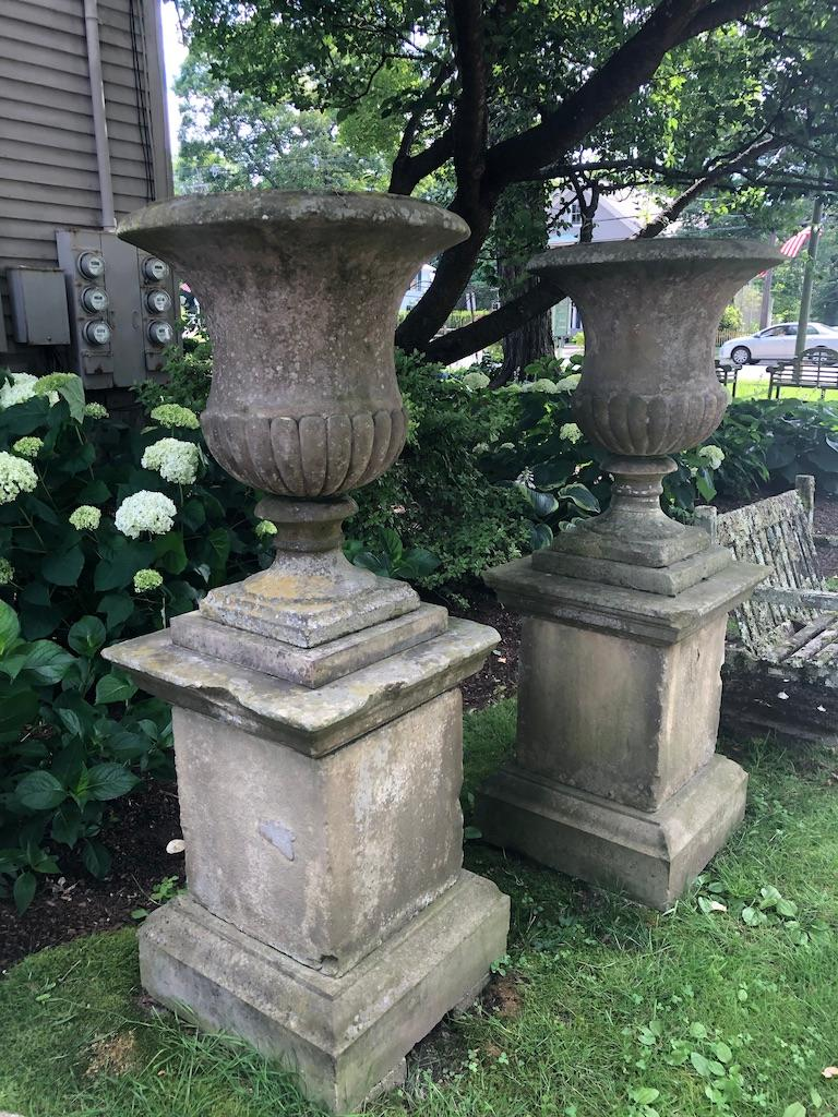 This is one pair of an amazing and stately set of four hand carved campana-form urns with quarter-lobed bodies and plain everted rims on their original tiered plinths. They originally decorated one of the Duke of Marlborough's gardens at Cornbury