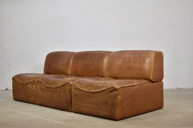Great sectional 'DS15' sofa designed by De Sede, Switzerland, 1970s. This set consist of three individual elements and is made out of very thick cognac saddle leather which has beautifully been aged over the years. The design is simplistic yet
