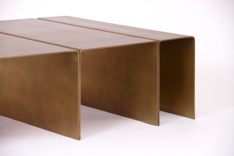 Contemporary coffee table made from solid brass in a burnished finish.  Sealed with a clear protective coating.  Also available in brushed aluminum and blackened steel.  Designed and made by hand in Los Angeles, California.