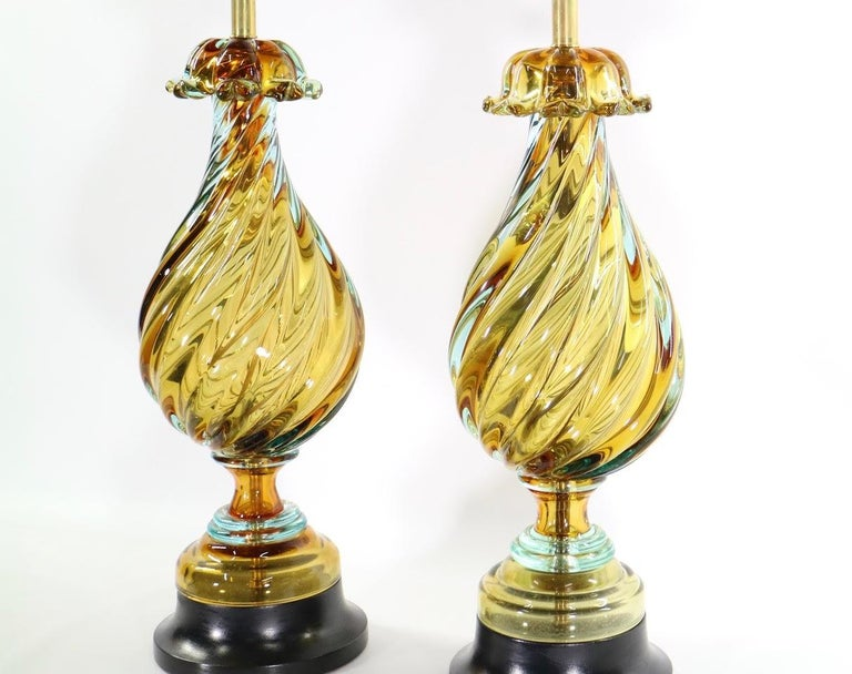 Pair of Hollywood Regency Murano lamps made by Seguso for Marbro Lamp Company. Seguso created this thick swirled glass lamp in a beautiful peridot green with aquamarine glass overlay on a ebonized wooden base. The pair comes with all new wiring and