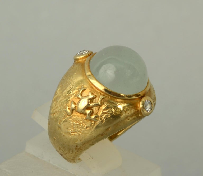 Whimsical and unusual 18 karat gold ring by Seidengang. The ring has an unexpected gold frog on one side and a turtle on the other. The central cabochon aquamarine has a diamond on either side. The gold has a nice molten texture. The ring is size 5