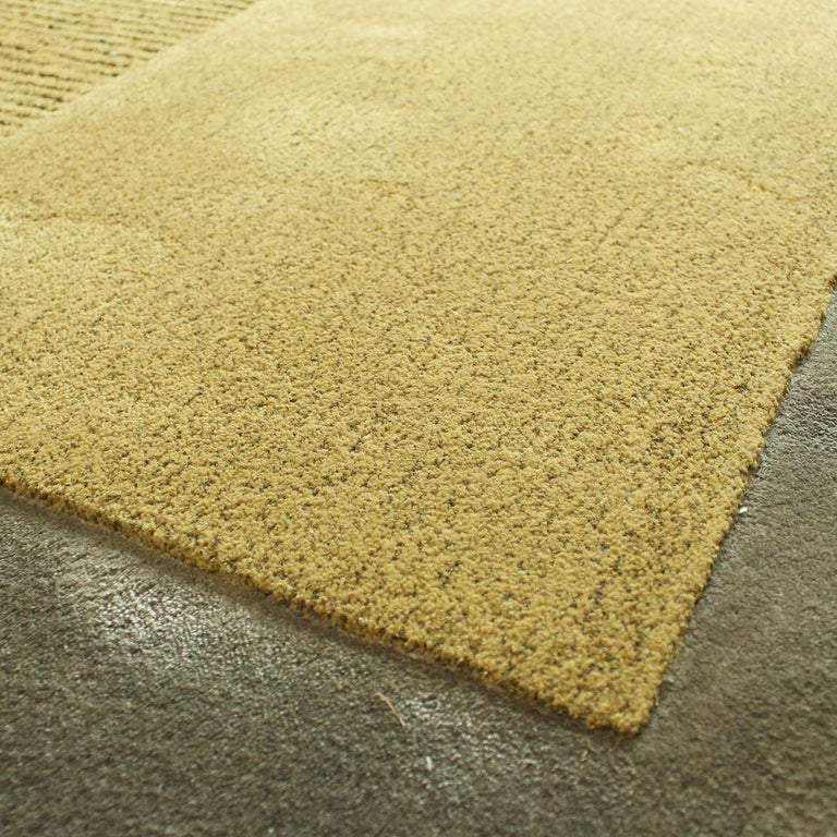 Warm greens, mustard yellow, and gray hues mix with bright yellow and red in this exquisite rug that combines an asymmetrical silhouette and a variety of textures obtained with the bouclè, velvet, relief, and shaggy techniques. The result is a
