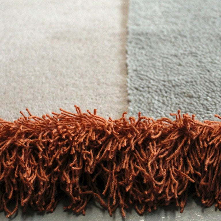 In a striking juxtaposition of textures, this asymmetrical rug is a stunning floor decoration that combines neutral, gray hues with accents in vibrant red and orange. This exquisite piece is part of the Selce Collection by Studio Solaris and made
