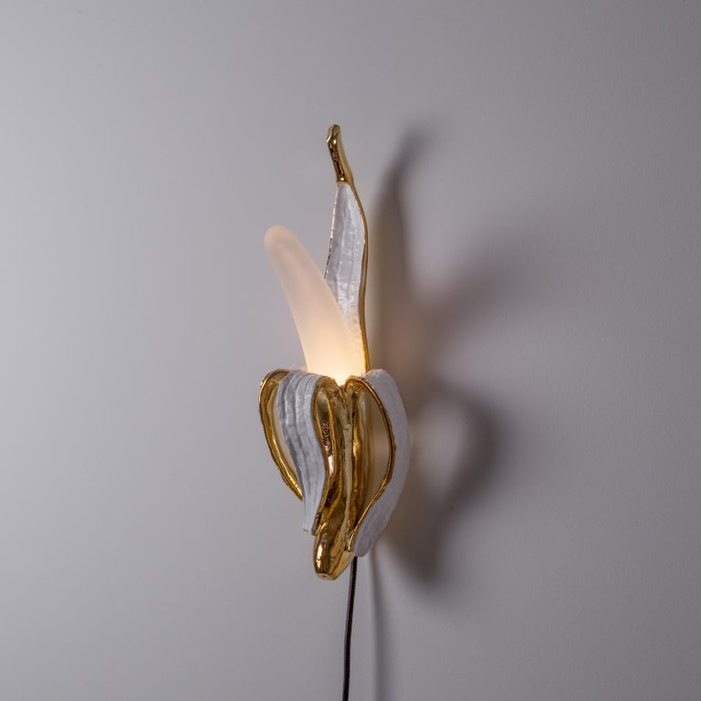 Banana Lamp by Studio Job in polished bronze is a symbol of outlandish creativity. Seletti and Unlimited edition has proposed it in four glass and resin versions: Huey, Dewey, Louie & Phooey.  - Dimmable lamp - Material: Resin, glass - Size: Cm