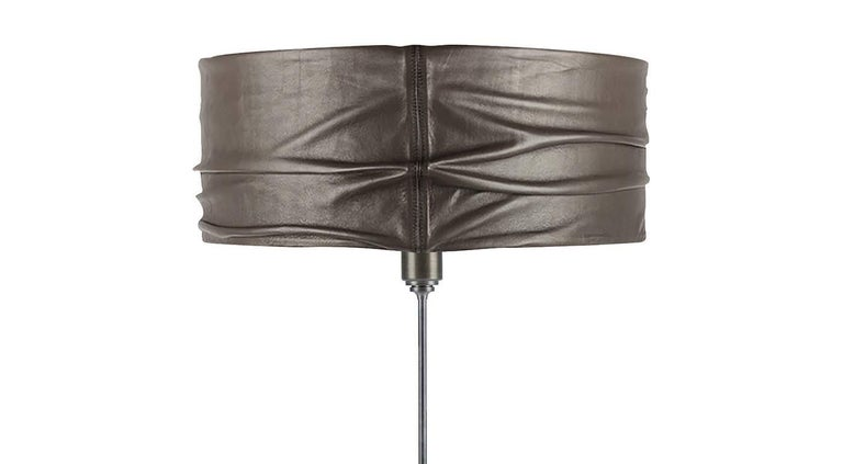 Rising from a solid marble base with a clean-lined silhouette, this table lamp is entirely handcrafted from skilled artisans. The structure is entirely made of steel and functions as a perfect, understated support for the captivating drum lampshade