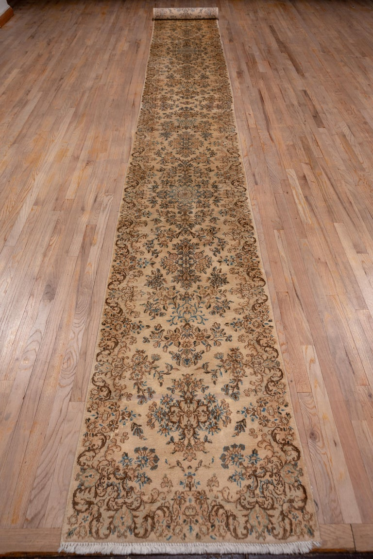 This good condition, well patinated SE Persian city runner shows a total old ivory ground with a flower spray and quatrefoil field pattern and open arabesque borders with small vases. Pistachio, cinnamon, off white, medium blue and rose are among