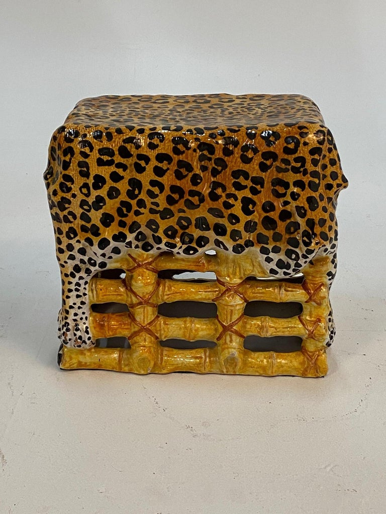 An unusual glamorous form of an Italian terracotta garden seat and table having leopard print draped over bamboo-esque base. Colors are warm gold and black, very striking.