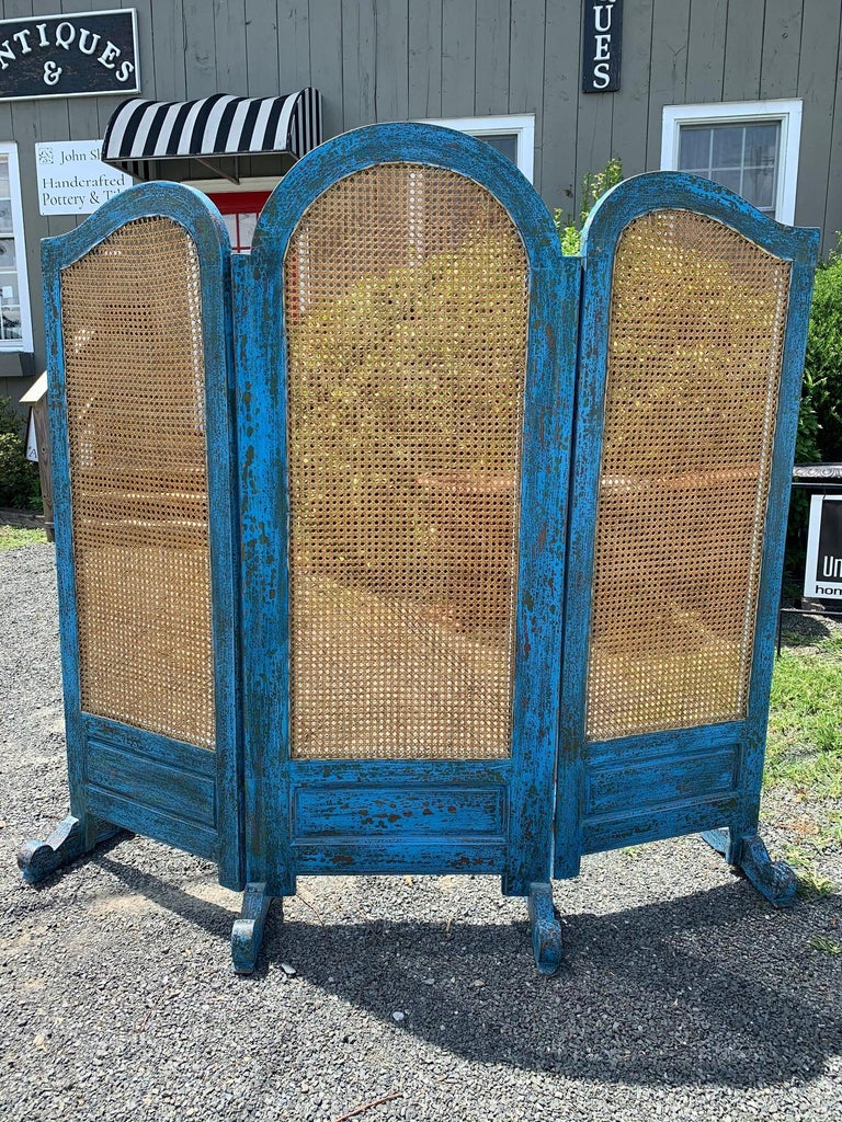"""A stunning 3 panel screen having turquoise Caribbean blue painted scrubbed wood frame and feet with natural colored caning on the panels. 71"""" H middle panel 68"""" H side panels."""