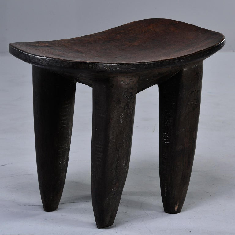 Senufo hand carved stool or side table features dark stained wood with a slightly curved top and thick, tapered legs, circa 1980s. The Senufo people are from Africa's Ivory Coast.