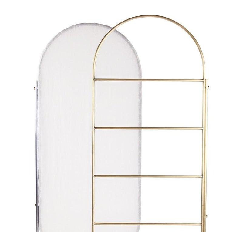 This versatile divider is a multi-functional piece of design that can be crafted in brass or varnished iron. It was made entirely by hand and its vertical metal frame mixes with the gentle curves of its top and bottom. The translucent natural fabric