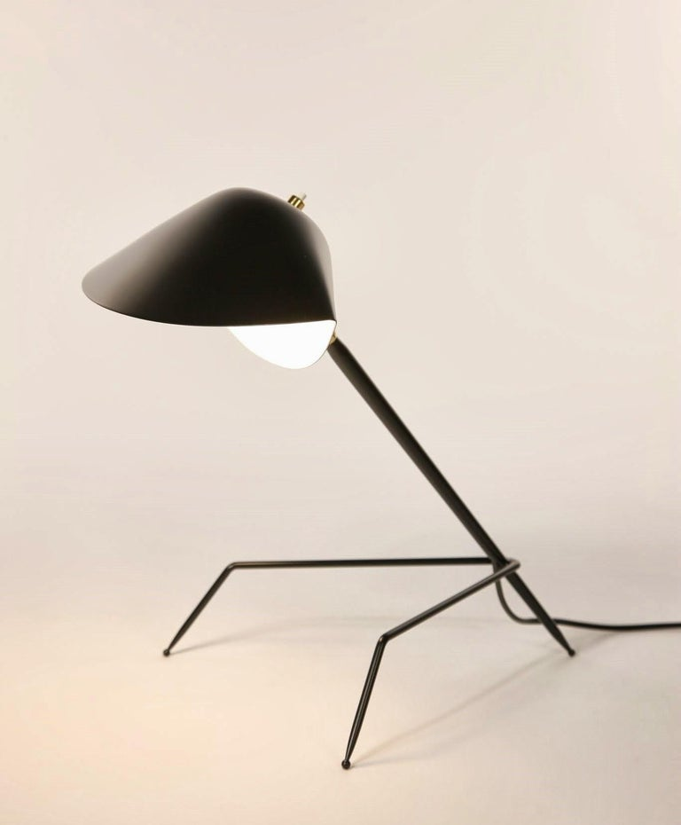 """This sconce is a certified re-edition, produced by the family of Serge Mouille on the site of his original workshop.  The shade of this lamp is modeled after a """"moule"""" or mussel shell. The arm is connected by a brass swivel and supported by an"""
