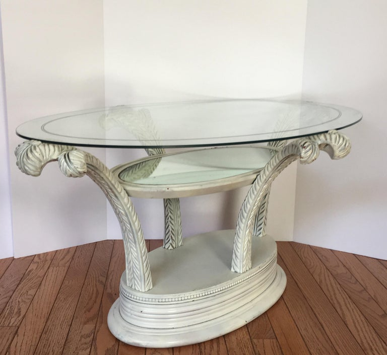 Glamorous Hollywood Regency sculptural coffee table featuring hand carved plumes or palm tree fronds. This occasional cocktail table has three tiers. The lowest tier is the wooden base and can house small knick knacks. The middle tier has original