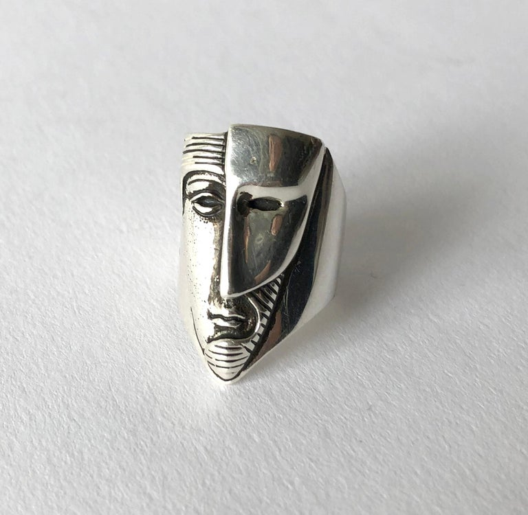 Mexican modernist sterling silver face with mask ring created by sculptor and jeweler Sergio Bustamante.  Ring is a finger size 6.  The face of the ring measures 1 1/8