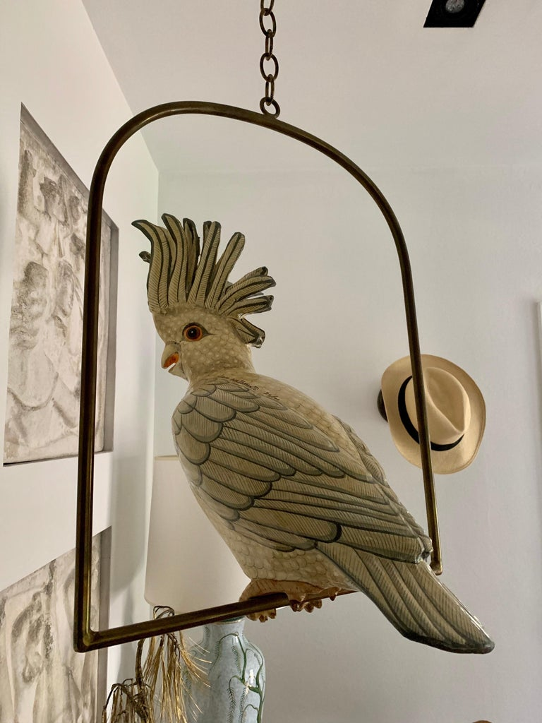 This is a limited edition series 26/100 papier mâché cockatoo sculpture by famed and highly collected Mexican artist, Sergio Bustamante. This large bird sits perfectly on the brass perch and can be hung at varying heights base on your needs. Total