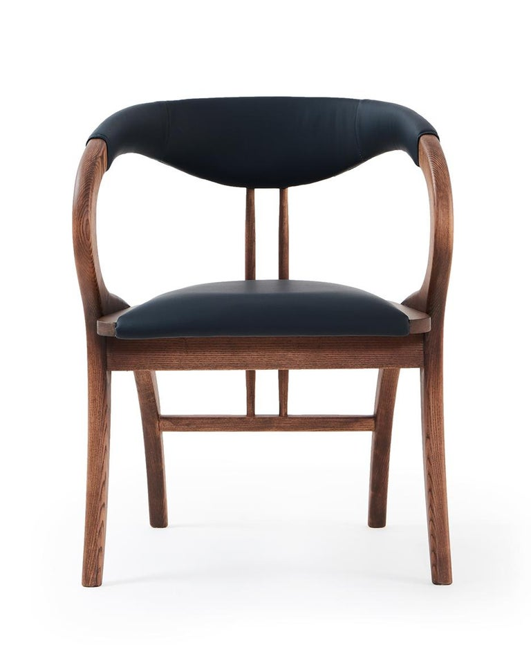The chair features extraordinary design with curved back legs that form part of the armrests and back support. Handcrafted of solid wood frame in walnut color and upholstered in black faux leather. Dimensions: 61 W x 57 D x 79 H cm. Seat height 48